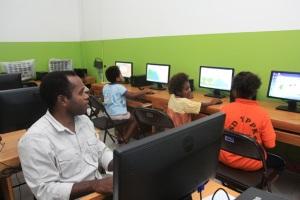 Tommy Tsolme (kiri) mengajari anak-anak belajar komputer di MPCC